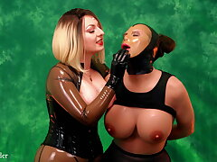 Popsy in latex playing adjacent to rubber sissy sex doll